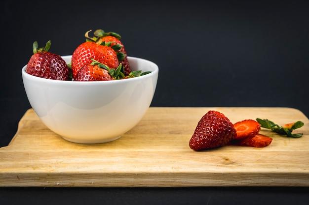 Ein erdbeerschnitt auf einem holz und eine weiße schüssel mit mehr erdbeeren, hausgemachtes erdbeerrezept