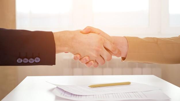 Ein erfahrener bankmanager und eine kundin schütteln sich die hände über dem tisch mit dem wohnungskaufvertrag und dem stift gegen die nahaufnahme des bürofensters