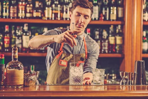 Ein erfahrener barmann macht einen cocktail im nachtclub oder in der bar.