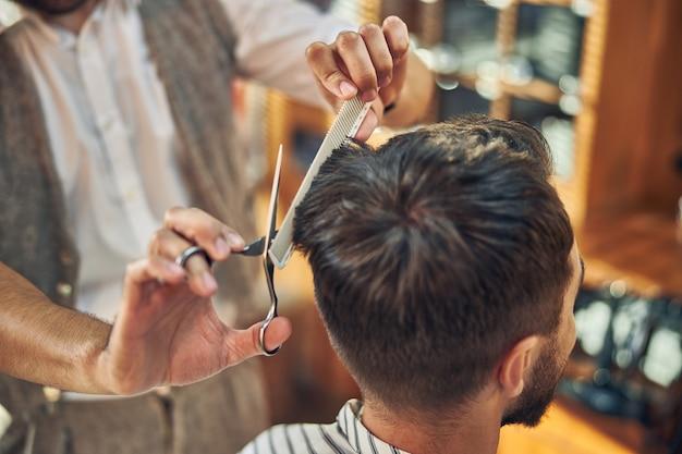 Ein erfahrener friseur, der eine schere und einen haarkamm hält, während er seinem kunden einen haarschnitt gibt