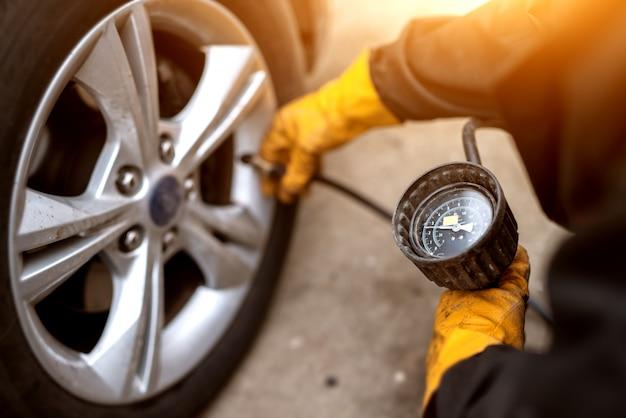 Ein erfahrener mechaniker in orangefarbenen handschuhen setzt ein luftventil auf ein autorad, um es unter druck zu setzen.