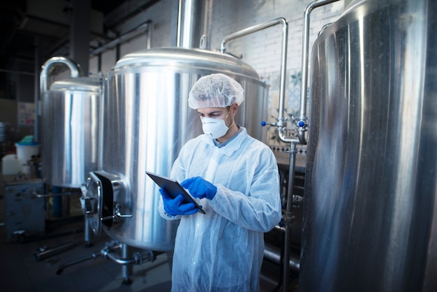 Ein erfahrener technologe in weißer schutzuniform, der tablette hält und die lebensmittelproduktion in der verarbeitungsfabrik kontrolliert