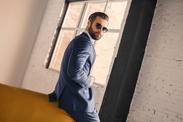 Ein erfolgreiches porträt eines angenehmen und jungen geschäftsmannes in sonnenbrille und stilvollem anzug, der ist
