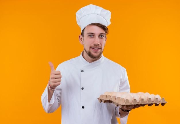 Ein erfreuter junger bärtiger kochmann, der weiße kochuniform und hut hält, die einen karton eier halten, während auf einer orange wand schauen