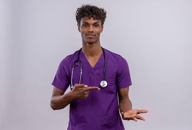 Ein erfreuter junger gutaussehender dunkelhäutiger arzt mit lockigem haar, der eine violette uniform mit stethoskop trägt, während er mit dem zeigefinger zeigt