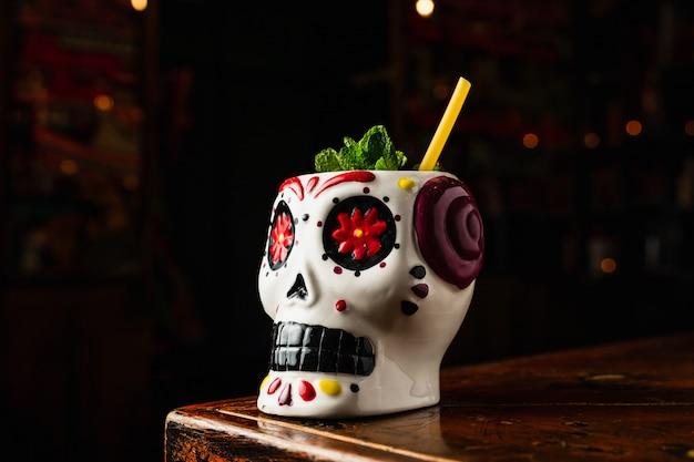 Ein erfrischender cocktail in einem tiki-scull-glas im mexikanischen stil mit einem öko-strohhalm aus spaghetti