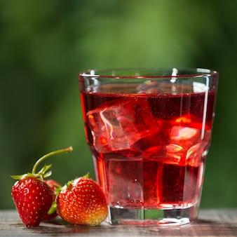 Ein erfrischendes sommergetränk mit erdbeeren und eiswürfeln neben einem glas sind die früchte von erdbeeren