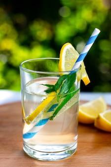 Ein erfrischendes zitronen-limetten-getränk mit trinkhalm auf einem holzständer