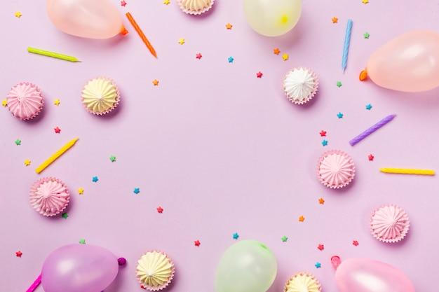 Ein erhöhter blick auf streusel; kerzen; ballons; aalaw auf rosa hintergrund