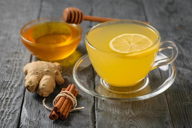 Ein erholsames vitamingetränk aus ingwerwurzel und zitrusfrüchten auf einem schwarzen tisch