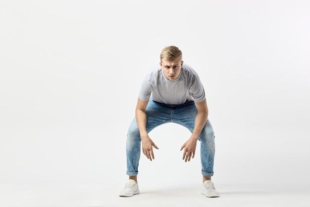 Ein ernster blonder kerl in einem weißen t-shirt und jeans steht mit den händen auf den knien on