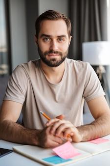 Ein ernster junger mann zu hause, der notizen schreibt, sitzt am tisch