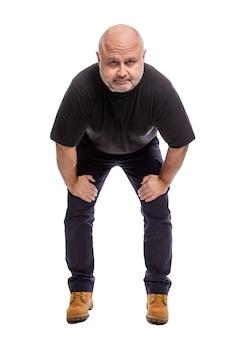 Ein ernster kahlköpfiger mann mittleren alters steht. isoliert weiß vertikale.