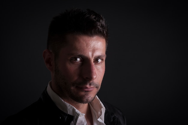 Ein ernster kaukasischer mann auf dunklem hintergrund