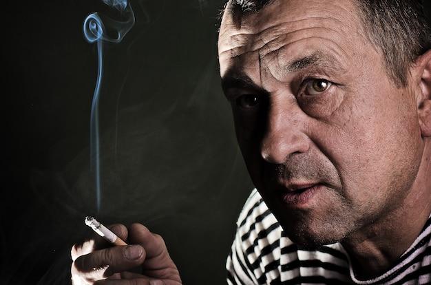 Ein ernster mann raucht eine zigarette in einem dunklen raum