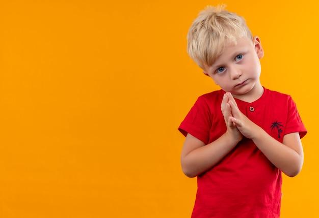 Ein ernster niedlicher kleiner junge mit blonden haaren und blauen augen, die rotes t-shirt tragen, während sie hand auf einer gelben wand zusammenhalten