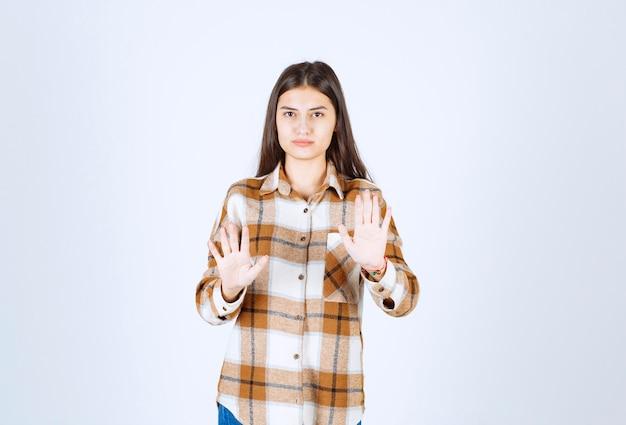 Ein ernstes modell des jungen mädchens, das stoppschild steht und zeigt