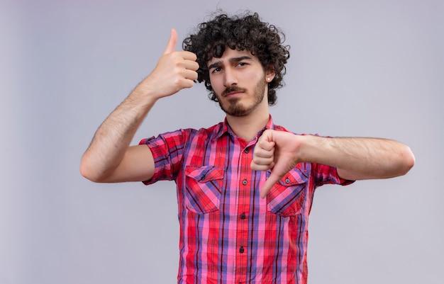 Ein ernsthafter gutaussehender mann mit lockigem haar im karierten hemd, das daumen auf und ab zeigt