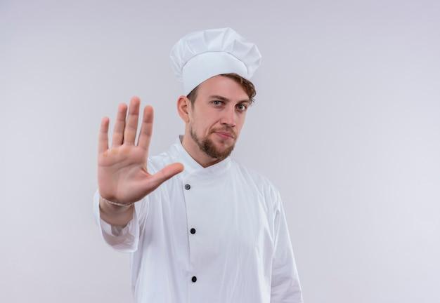 Ein ernsthafter junger bärtiger kochmann, der weiße kochuniform und hut trägt, die stoppgeste mit hand zeigen, während auf einer weißen wand schauen