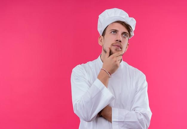 Ein ernsthafter junger bärtiger kochmann in der weißen uniform, die denkt, während hand an seinem kinn auf einer rosa wand hält