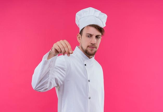 Ein ernsthafter junger bärtiger kochmann in der weißen uniform, die kochmütze trägt, die gewürze auf teller auf einer rosa wand besprüht