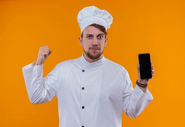 Ein ernsthafter junger bärtiger kochmann in der weißen uniform, die leerzeichen des handys beim betrachten auf einer orange wand zeigt