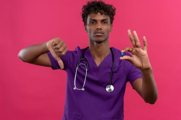 Ein ernsthafter junger gutaussehender dunkelhäutiger arzt mit lockigem haar in violetter uniform mit stethoskop, das beim halten der pille die daumen nach unten zeigt