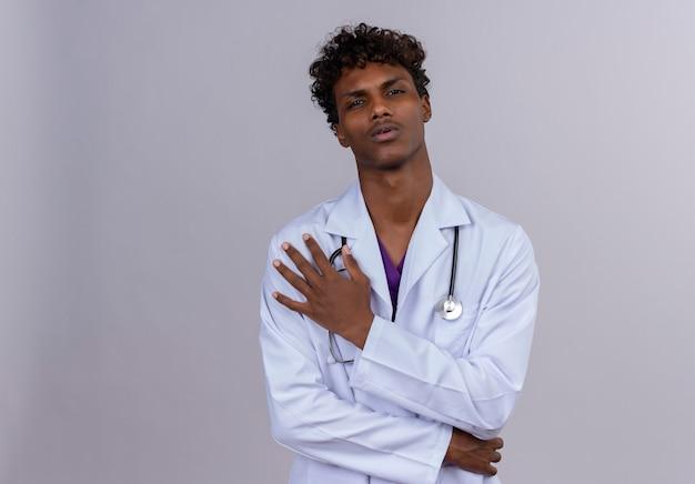 Ein ernsthafter junger gutaussehender dunkelhäutiger männlicher arzt mit lockigem haar, der weißen kittel mit stethoskop trägt, das herzschmerz oder brustschmerzen leidet