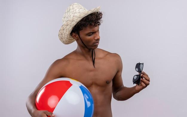 Ein ernsthafter junger gutaussehender dunkelhäutiger mann mit lockigem haar, der sonnenhut trägt und sonnenbrille betrachtet, während aufblasbarer ball hält