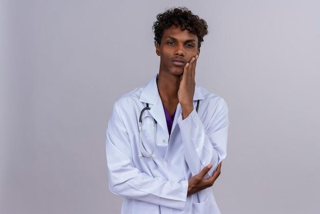 Ein ernsthafter junger hübscher dunkelhäutiger männlicher arzt mit lockigem haar, der weißen kittel mit stethoskop trägt, das hand auf wange hält