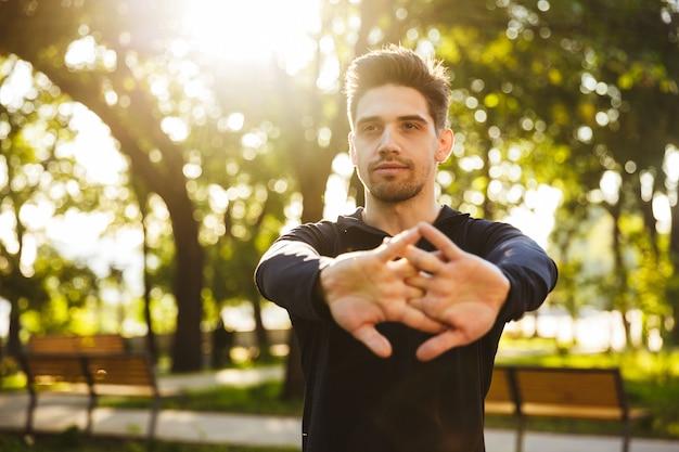 Ein ernsthafter junger sport-fitness-mann, der in der grünen parknatur steht, macht dehnübungen für die arme.