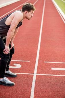 Ein erschöpfter männlicher athlet, der auf rennstrecke sich entspannt