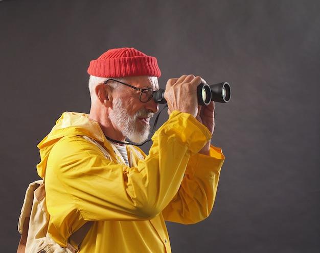Ein erstaunlicher mann, ein mann mit einer roten mütze und einem leuchtend gelben regenmantel genießt die aussicht auf smortya in der ferne mit einem fernglas, isoliertem hintergrund. hobby