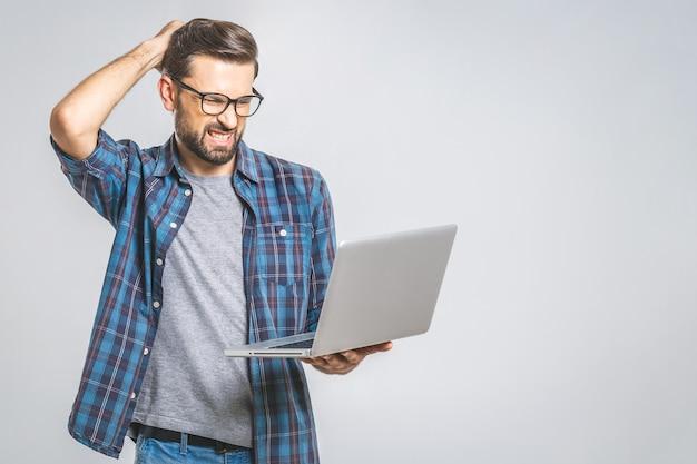 Ein erstaunter junger mann hat einen softwarefehler. auf grauer wand isoliert.