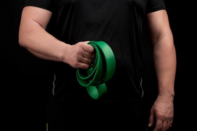 Ein erwachsener athlet mit einem muskulösen körper in schwarzer kleidung macht körperliche übungen mit sportgrünem gummi