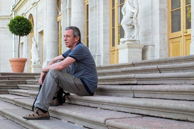 Ein erwachsener kaukasischer rentner in sommerkleidung sitzt und ruht auf den stufen eines alten historischen hauses. lokaler tourismus. alleinreisend. selektiver fokus.