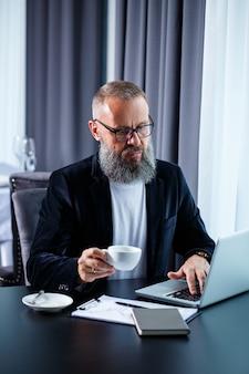 Ein erwachsener männlicher geschäftsmann arbeitet an einem neuen projekt und betrachtet die aktienwachstumsdiagramme. sitzt am tisch am großen fenster. schaut auf den laptop-bildschirm und trinkt kaffee.