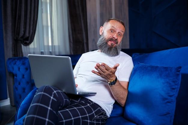 Ein erwachsener männlicher geschäftsmann arbeitet an einem neuen projekt und betrachtet die aktienwachstumsdiagramme. sitzt am tisch am großen fenster. schaut auf den laptop-bildschirm