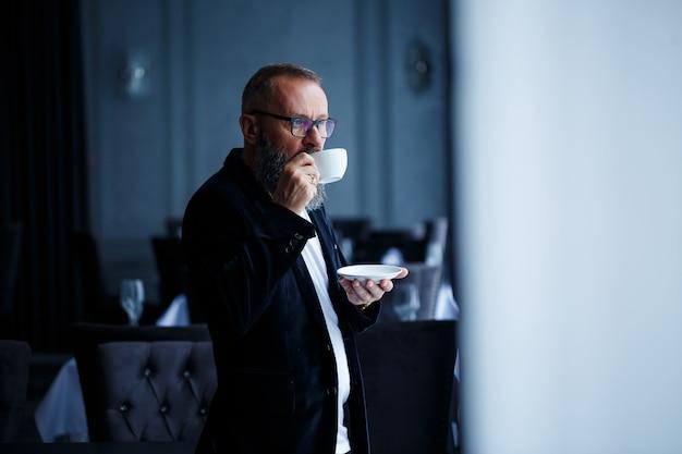 Ein erwachsener männlicher mentor, direktor, geschäftsmann in gläsern und anzug trinkt kaffee und ruht sich aus. konzept des arbeitstages