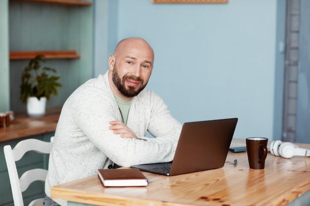 Ein erwachsener mann, der an einem computer in der küche arbeitet