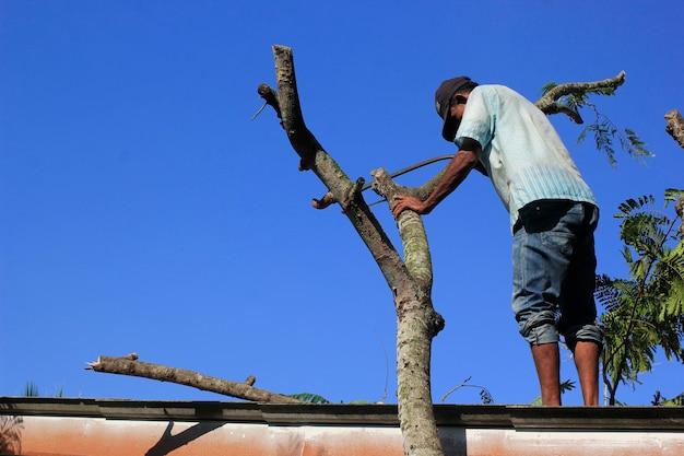 Ein erwachsener mann fällt einen baum, der das dach des hauses blockiert.