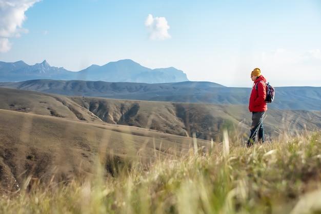 Ein erwachsener mann mit einem rucksack steht in den bergen.
