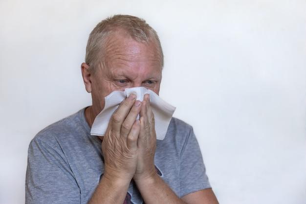 Ein erwachsener mann putzt sich die nase und niest in eine papierserviette