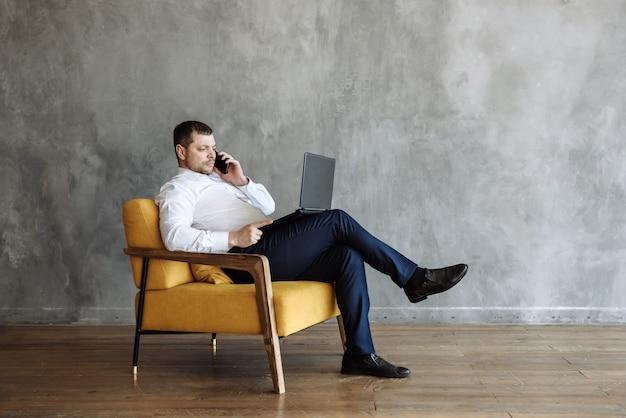 Ein erwachsener mann sitzt mit einem laptop auf einem stuhl und telefoniert
