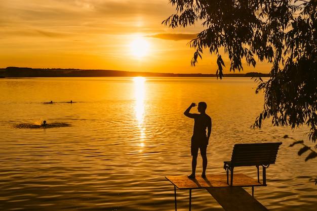 Ein erwachsener mann steht auf dem hölzernen mauerwerk nahe dem fluss und betrachtet sonnenuntergang