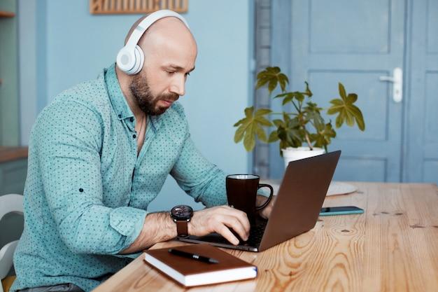 Ein erwachsener mann trinkt kaffee und tippt auf einem laptop, arbeitet online, macht zu hause geschäfte
