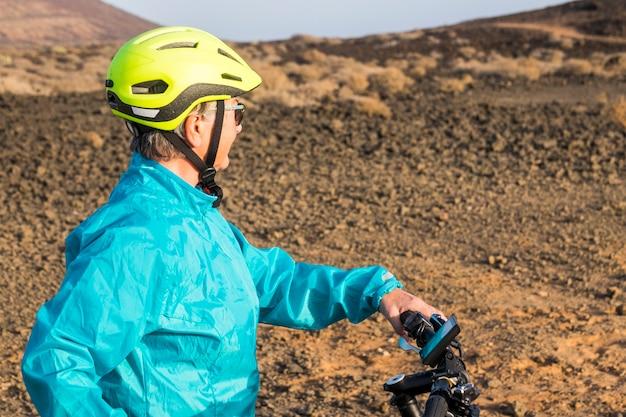Ein erwachsener und ein senior in einem felsigen berg, der mit einem fahrrad trainiert - aktive reife frau, die aktivität macht