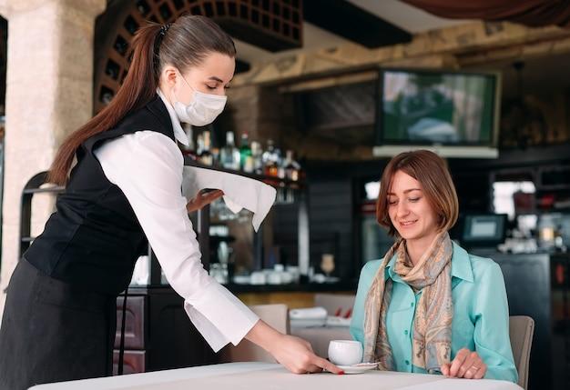 Ein europäisch aussehender kellner in einer medizinischen maske serviert kaffee.