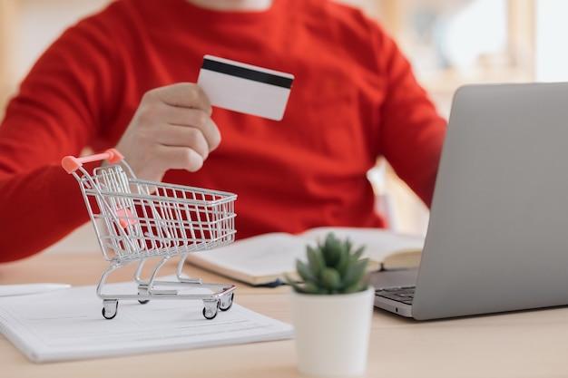 Ein europäischer mann in einem roten pullover kauft online essen oder liefert einkäufe