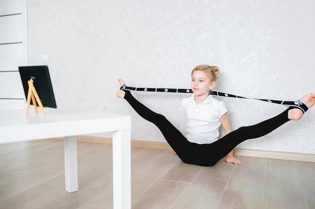 Ein europäisches schulmädchen macht dehnübungen mit einem gummiband und sieht sich online-videos auf einem laptop an. gymnastik, choreografie. selbstisolation, quarantäne, online-bildung